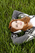 Young fashion girl with headphones lying at green spring grass.
