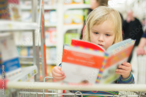 Adorable baby with book near book stand in supermarket