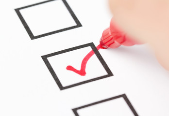 Hand drawing red check mark in checklist box