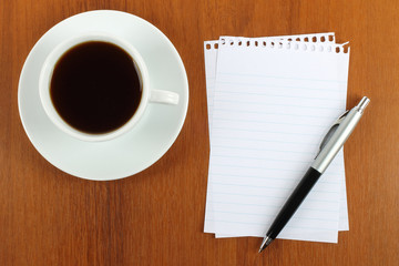 Cup of coffee, paper and pen on wooden background