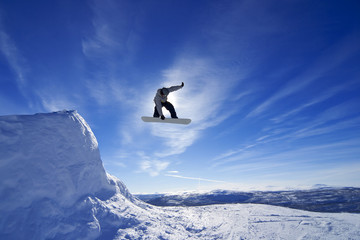 Amateur snowboarder making a grab in big air jump.
