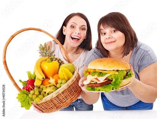 Women choosing between fruit and hamburger.