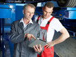 Master mechanics inspecting the engine of a car with touchpad
