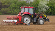 Small scale farming with tractor and plow in field. Agricultural