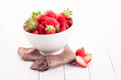 Strawberries inside bowl on white table