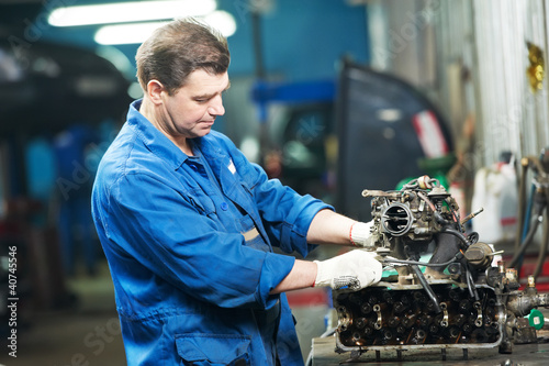 auto mechanic at repair work with engine