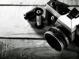 Vintage 35 mm film photo camera over wooden desk