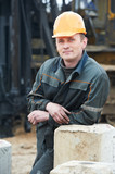 builder in dirty workwear at construction site poster