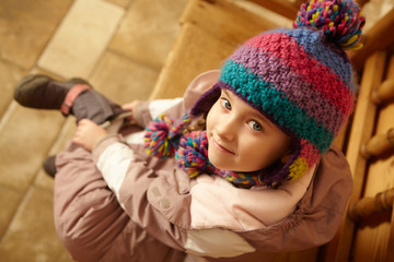 Young Girl Sitting On Wooden Seat Putting On Warm Outdoor Clothe