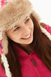 Portrait Of Teenage Girl In Snow Wearing Fur Hat