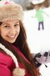 Teenage Couple Having Snowball Fight Wearing Fur Hats