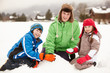 Group Of Children Building Snowman Wearing Woolly Hats