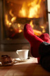Close Up Of Mans Feet Relaxing By Cosy Log Fire With Tea And Cak