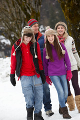 Teenage Family Walking Along Snowy Street In Ski Resort