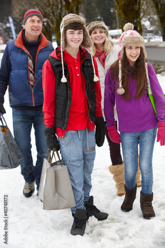 Teenage Family Carrying Shopping Walking Along Snowy Street