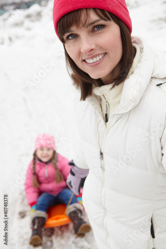 Mother Pulling Daughter On Sledge On Snowy Street In Ski Resort