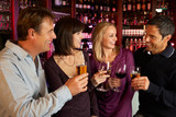 Fototapety Group Of Friends Enjoying Drink Together In Bar