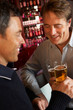 Two Men Enjoying Drink Together In Bar