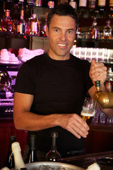 Portrait Of Barman Standing Behind Bar Pouring Beer