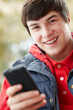 Teenage Boy Texting On Smartphone Wearing Winter Clothes