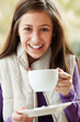 Teenage Girl In Outdoor CafŽ With Hot Drink  Wearing Winter Clot