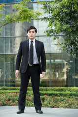 Asian business man standing outside.