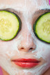 Closeup photo of girl with cucumbers on her eyes and facial mask