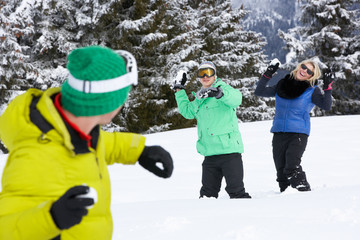 Group Of Young Friends Having Snowball Fight On Ski Holiday In M