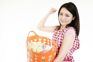洗濯ものを持ちガッツポーズをする女性