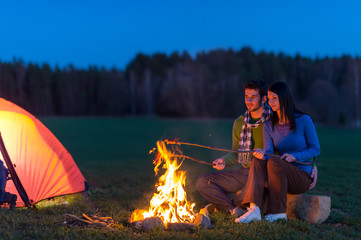 Camping night couple cook by campfire romantic