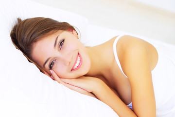 smiling girl lying on the bed
