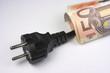 Enchufe con billetes de euro enrollados