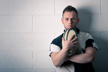 Rugby player against white wall.