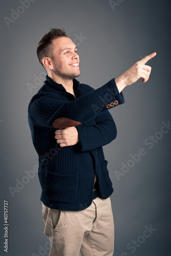 Happy casual man finger pointing over grey background.