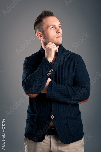 Confident casual man waiting over grey background.