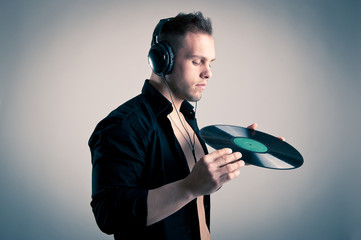 Young man working as dj with ear-phones and disc.