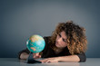 Young girl looking at a world globe wishing to have a vacation.