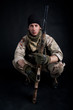 Soldier with rifle against black background. Full body.