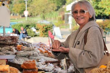 a senior woman  in an open-air market