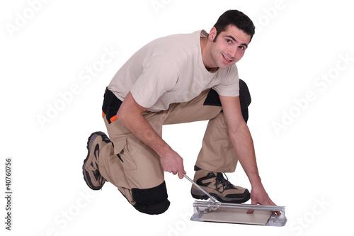Man kneeling to cut tile to size