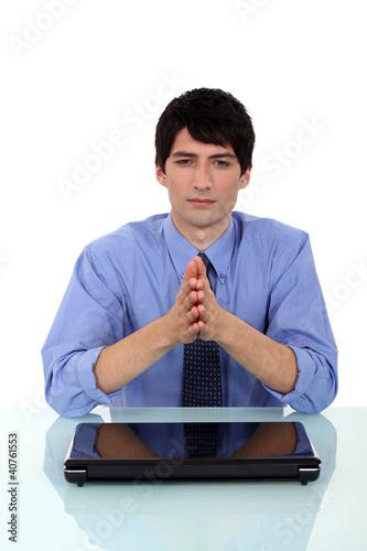 Businessman praying at desk