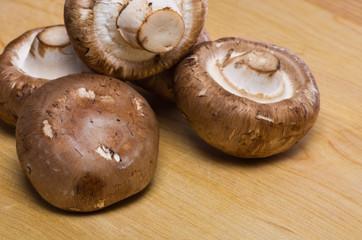 Five Portobello mushrooms on cutting board