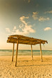 wooden canopy on the sandy beach and blue sky yellow tone