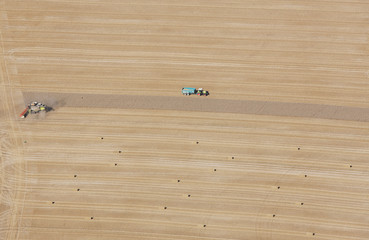 Aerial view of tractors at work in crop fields