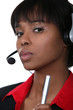 An African American businesswoman with a headset on.