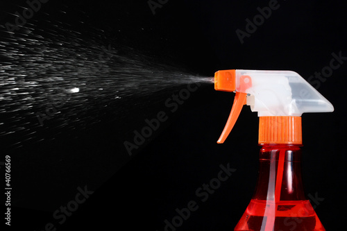 spray bottle and spraying on black background