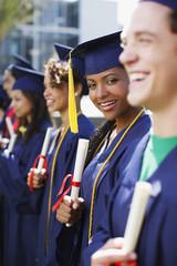 Graduates holding diplomas outdoors