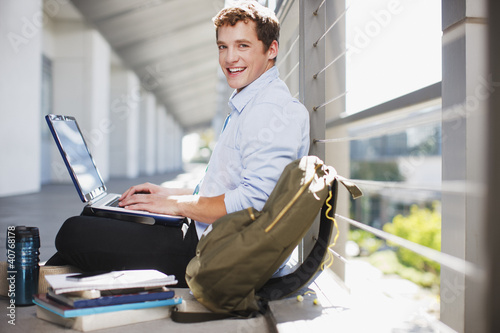 Student working on laptop on floor