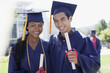 Graduates with diplomas smiling together