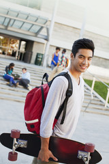Student carrying skateboard outdoors
